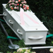 Royalty-Free Stock Photo: White coffin with pink sympathy flowers
