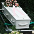 Stock Photo: White coffin with pink sympathy flowers