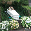 White coffin with pink sympathy flowers - Stock fotografie