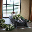 White coffin with sympathy flowers — Stock Photo