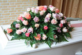 White coffin with pink sympathy flowers — Stockfoto