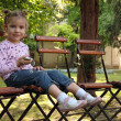 Little girl sitting in the  park and listen music on phone — Stockfoto
