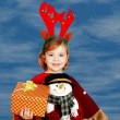 Little girl with rudolf deer horn on head and gift — Stock Photo