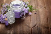 Spa minerals and flowers on wood background — Stock Photo