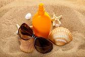 Summer beach - suntan oil and dark glasses on sand — Stock Photo