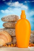 Sunbath - suntan oil, shell and stones — Stock Photo