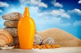 Sunbath - suntan oil on beach — Stock Photo