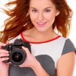 Woman in gray dress wit digtal camera on white — Stock Photo
