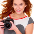 Woman in gray dress wit digtal camera on white — Stock Photo #7724089