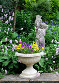 Stone Flower container with pansies and a stone statue — Stock Photo