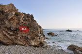 岩石海岸线与国旗的土耳其阿拉尼亚 — 图库照片