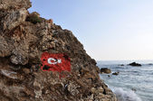 Rock coastline in Alanya with flag of Turkey — Stock Photo