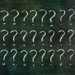 Stock Photo: Question marks on grungy blackboard.