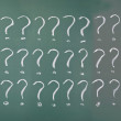 Stock Photo: Drawing question marks on blackboard.
