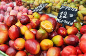 Mango and plums on market stand — Stock Photo