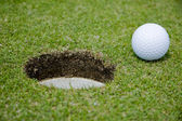 Golf ball very close to a hole — Stock Photo