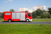 Panning image of a fire truck rushing on the street — Stock Photo