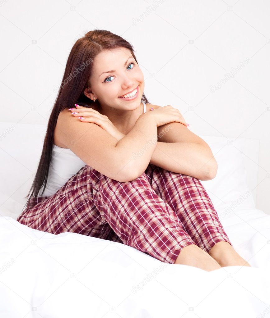 Happy beautiful brunette girl sitting on the bed at home   — Stock Photo #6775549