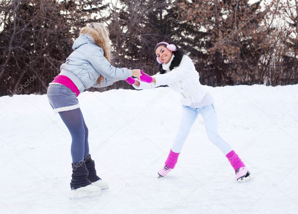 Two beautiful girls learning ice skating outdoor on a warm winter day — Stock Photo #7511927