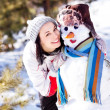 Woman with a snowman - Stock Photo