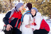 Couple with a snowman — Stock Photo