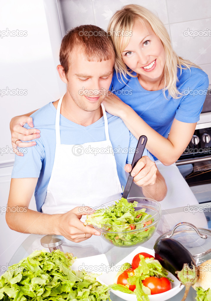 Happy young couple cooking together in the kitchen at home — Stock Photo #7956563