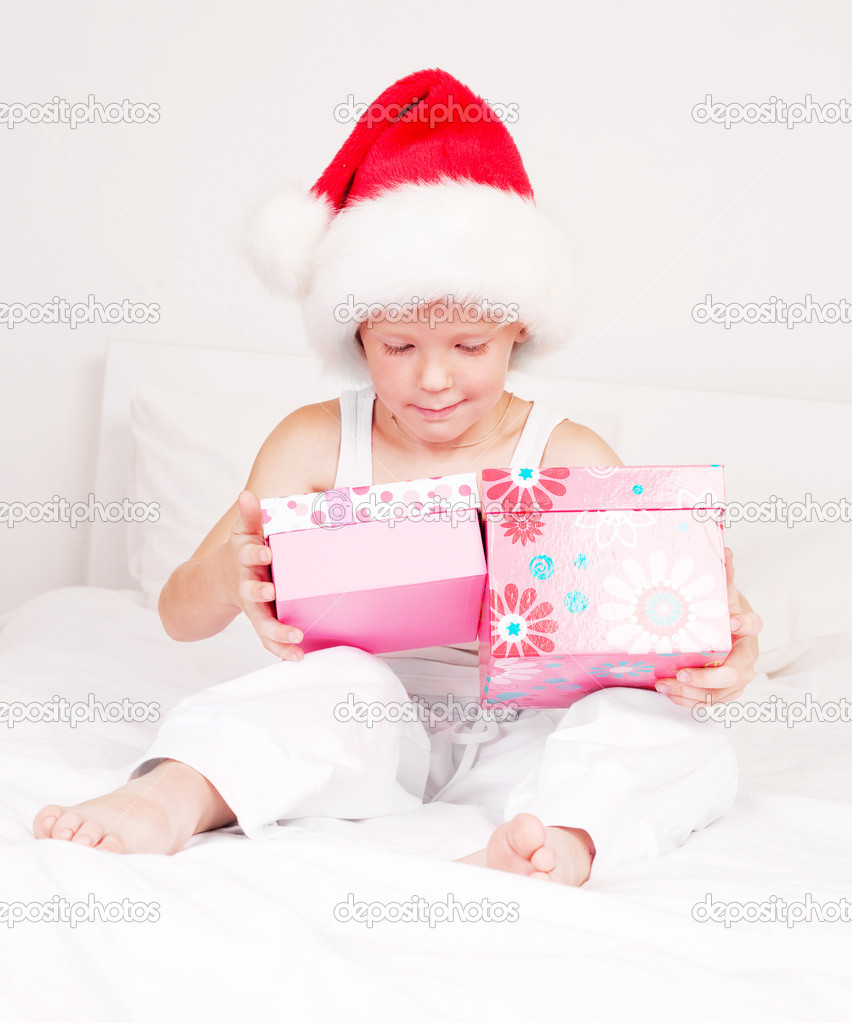Little boy celebrating Chritmas and opening presents  on the bed at home — Lizenzfreies Foto #7956578