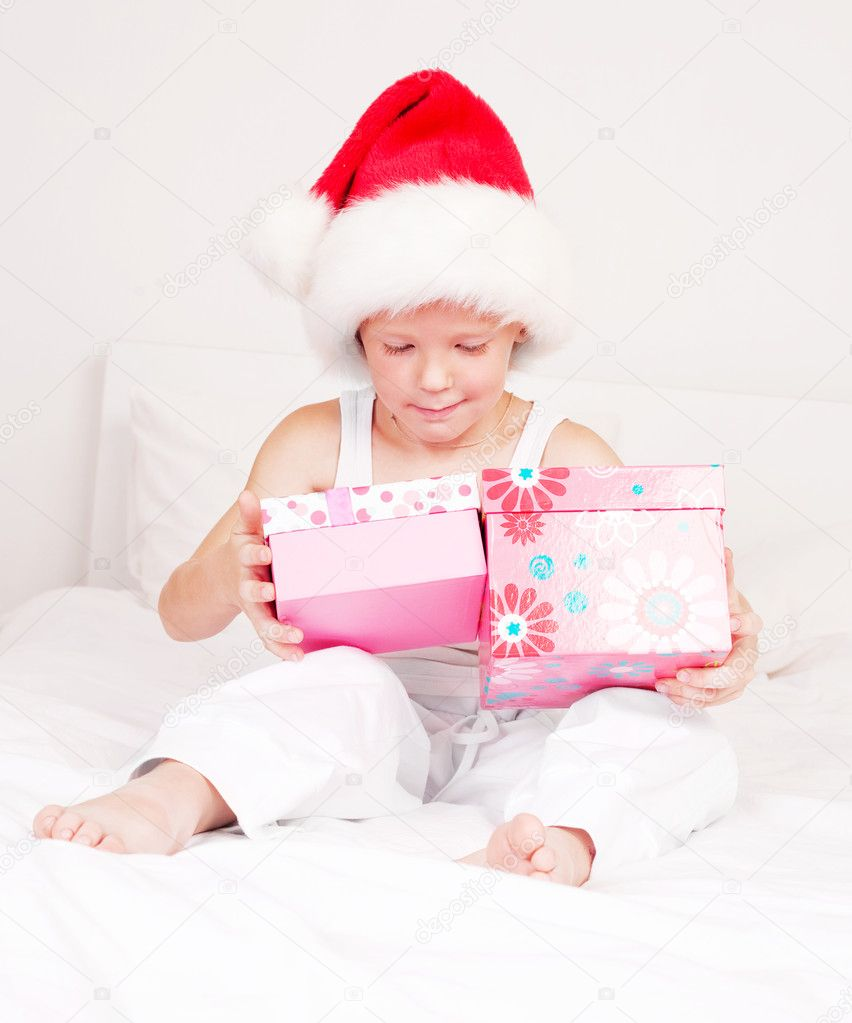 Little boy celebrating Chritmas and opening presents  on the bed at home — Stok fotoğraf #7956578