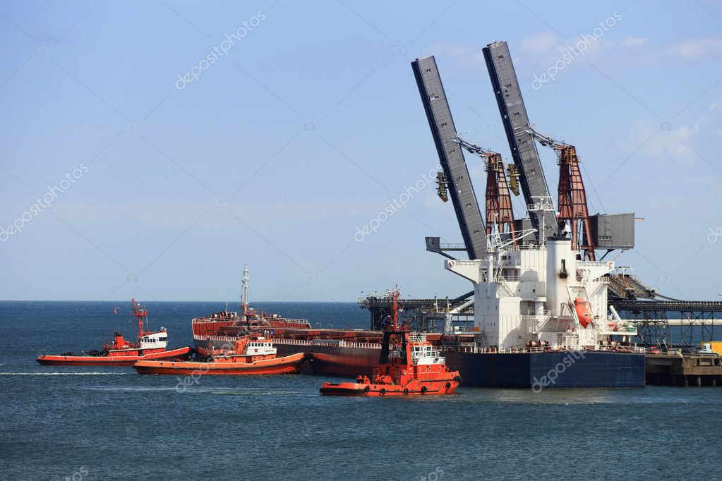 Tug boats pushing a cargo ship to port. — Stock Photo #6837498