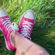 Pink sneakers on girl legs on grass - Stock Photo
