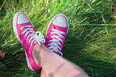 Pink sneakers on girl legs on grass — Stock Photo