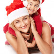 Mother and daughter in Santa Claus's hats - Stock Photo