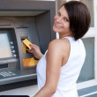 Woman withdrawing money from credit card at ATM — ストック写真