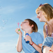 Boy and mother with soap bubbles against a sky — Stock Photo