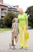 Mor och son gå med kassar och påsar — Stockfoto