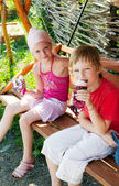 Two children eating ice cream in park — Stock Photo