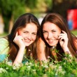 Two girlfriends in park with a mobile phones — Stock Photo #7314678