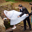 Newlyweds drink water from a spring in the woods - Stock Photo