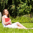 Girl-student sit on lawn and reads textbook — Stock Photo