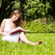 Girl-student sit on lawn and reads textbook — Stock Photo #7314938