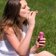 Young girl blowing soap bubbles in summer green park — Stock Photo