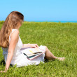 Girl-student sit on lawn and reads textbook — Stock Photo #7314944