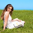 Girl-student sit on lawn and reads textbook — Stock Photo #7314946