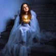 Angel with a candle sitting on the stairs — Stock Photo