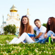 Small group of students in a clearing in background of church — Stock Photo