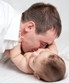 Happy family, father and baby on the white bed — Stock Photo