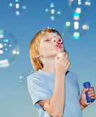 Boy with soap bubbles against a sky — Stock Photo