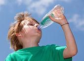 Sede menino bebendo água fresca ao ar livre — Foto Stock