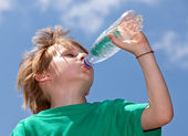 Thirsty boy drinking fresh water outdoors — Foto Stock