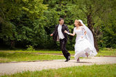 Happy bride and bridegroom running along the alley in the park — Stock Photo
